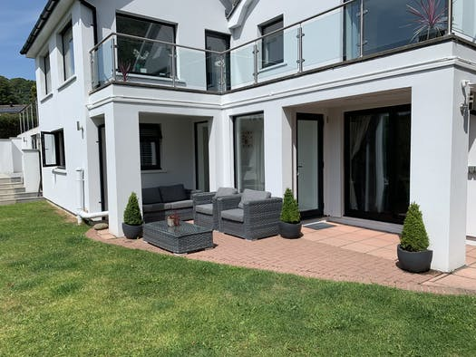 Patio area at Garden Flat with two outside chairs and sofa and table. Lawns and potted plants