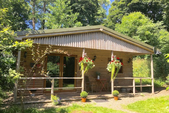 Cabin with wooden veranda area and double glass door entrance, hanging baskets