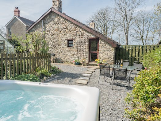 Exterior of Ty Clyd with path to hot tub and table and chairs