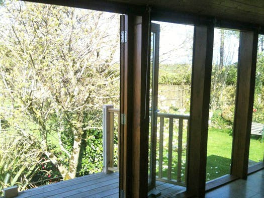 Patio door opening from Chestnut cottage onto a balcony overlooking the garden.