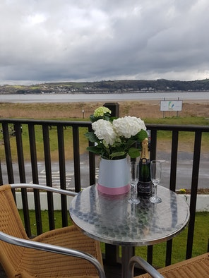 Table and chairs on the balcony at 5 Innisfree Cottages overlooking the estuary