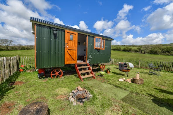 Outside view of Bubbleton Farm Shepherds Hut with picnic table and chairs, barbeque