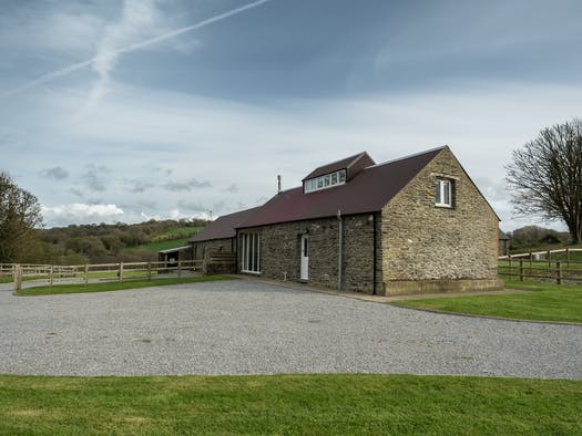 Outside view of barn with gravel driveway and lawns