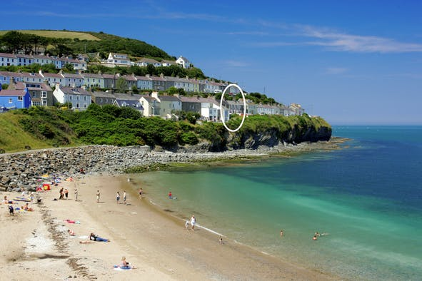 People on the beach with sea on right and streets of terraced houses on hill behind