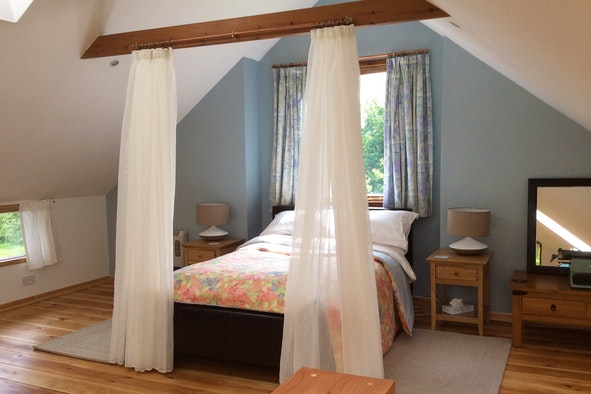 Sleeping area with double bed, curtains at foot of bed, dressing table and beside tables and lamps
