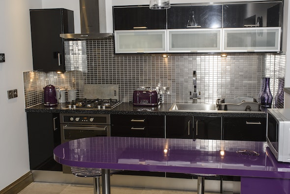 kitchen area with purple accessories, breakfast bar, gas hob, electric oven, toaster and microwave