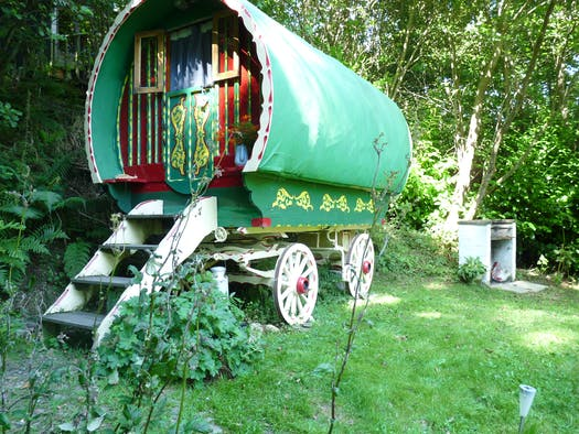 Romany Wagon Retreat surrounded by lawns and trees, barbecue