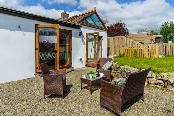 Outside seating area showing patio doors, low table, cane sofa and chairs