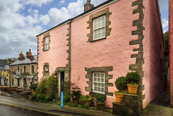 Exterior of The Old Cottage, a large pink house with a small front garden