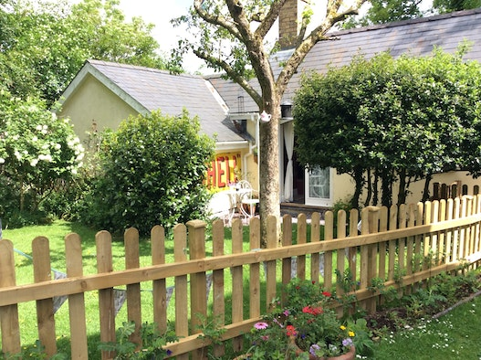 The Cwtch viewed through a fence with lawn, flower beds, shrubs and seating area