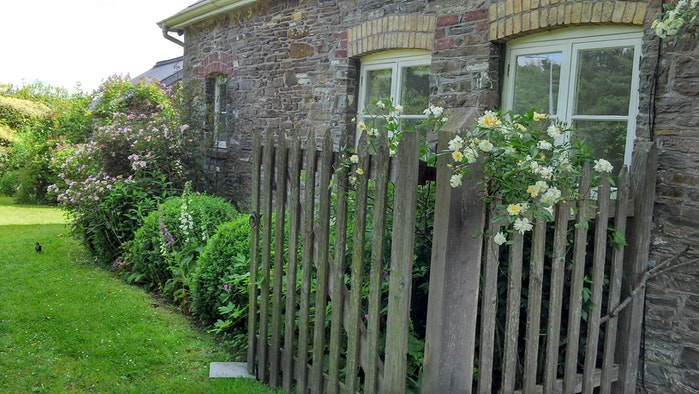 cottage exterior with a fence alongside it and pretty flowers with a glimpse into the garden