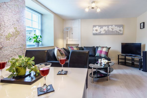 Dining table with glasses of wine, 4-seater L-shaped sofa, flat screen TV and coffee table
