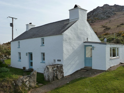 Exterior of Tal y Gaer, a tradition white cottage with Garn Fawr in the background