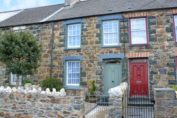 View of the front of Orielton, stone mid-terrace cottage with sage green front door