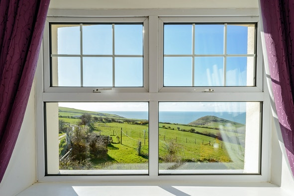 Sea view beyond fields through the window of the Farmhouse at Ffynnon Grog