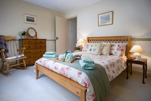Double bed, rocking chair, chest of drawers, mirror, bedside cabinet and lamp