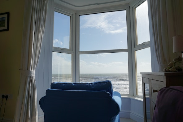 Armchair in the bay window looking over the sea