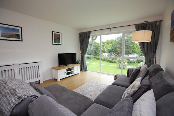 Lounge with sofa, tv, floor to ceiling windows overlooking garden