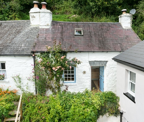 Cae'r Aber a white cottage with a light blue door
