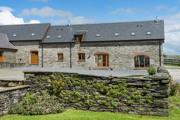Outside view of Ysgubor Isaf with stone wall, parking area and front of cottage