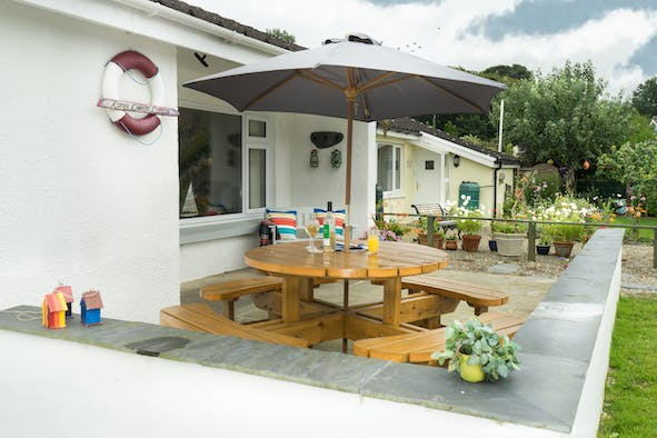 Patio with picnic table, umbrella and bench
