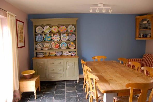 Dining table and chairs with a Welsh dresser and colourful plates