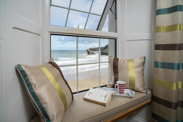 Cushions, book and a cuppa on the window seat looking out onto the sea view