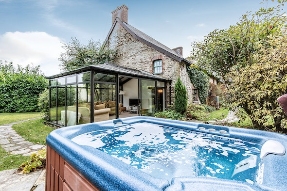 Hot tub with view towards The Farmhouse conservatory and building