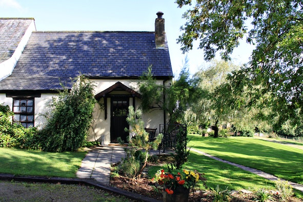 Exterior of Snowdrop Cottage with lawn to the side and front, flower beds each side of path