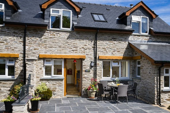 Outside view of Teifi Cottage with patio and picnic table and chairs