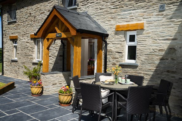 Front of Towy Cottage with paved patio, table and chairs