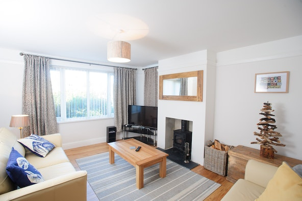 Caerllan living room with sofas, coffee table, TV, logburner and large window