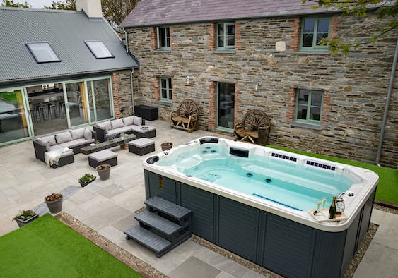 Outside view of Towyn Farmhouse with hot tub, outside seating area and lawn