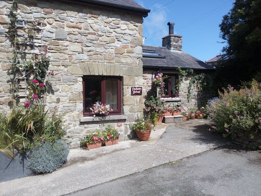 Fedwen Uchaf, a traditional stone cottage with parking in front and containers of colourful flowers