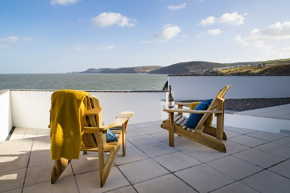 Two wooden deck chairs on the patio looking out to sea in Clifftop Haven