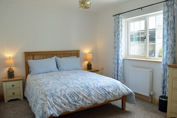 Double bedroom in Driftwood, bed, bedside cabinets, lamps, radiator and window