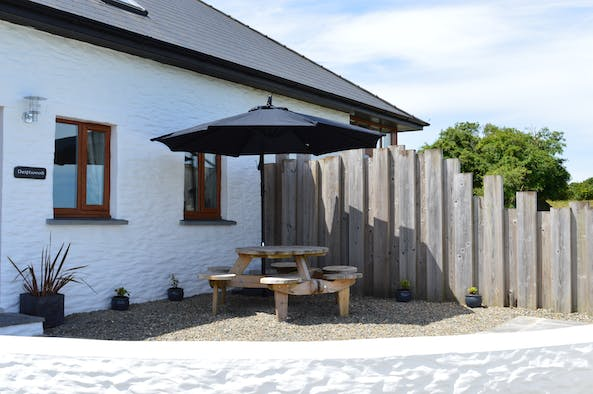 Patio area at Driftwood with picnic table and parasol