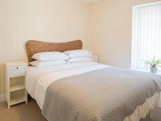 double bed in a neutral room with wicker headboard and grey throw