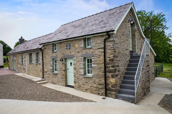 Outside view of Bwthyn Briallen with gravel area, front door and stone steps to first floor
