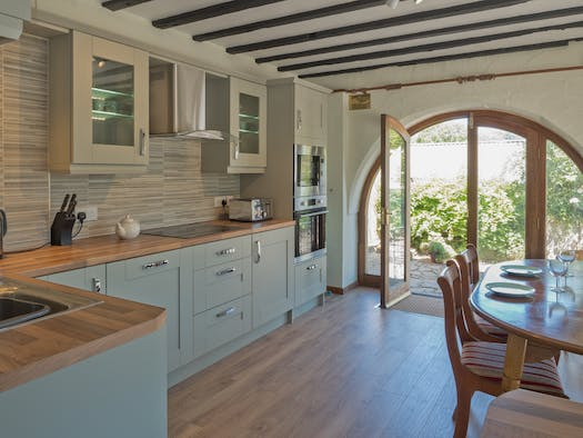Kitchen cabinets, dining table and chairs and arched doorway to garden
