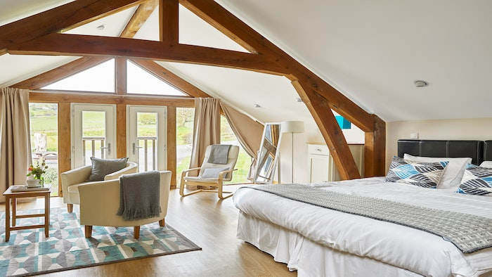 luxury bedroom with seating area and view of the grounds through the balcony doors