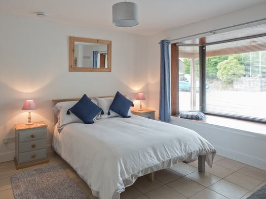 Double bed, bedside cabinets and lamps and window seat