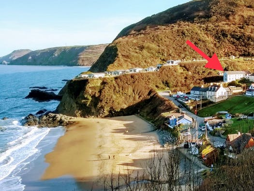 View from the coastal path across Tresaith Beach and a marker showing the position of Brigydon