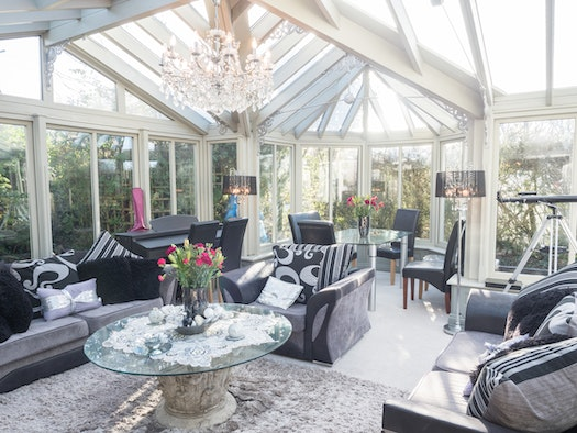 Table and chairs, sofas, armchairs, telescope, coffee table and flowers in the Conservatory
