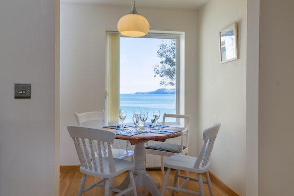 Dining table laid for lunch with 4 chairs and a view to the sea