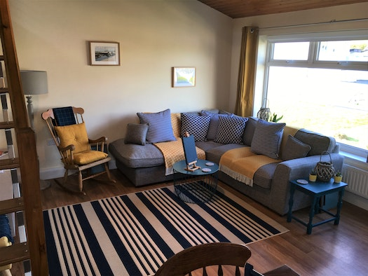 Living area in Plas Teifi with corner sofa, wooden rocking chair, side tables, window and stairs