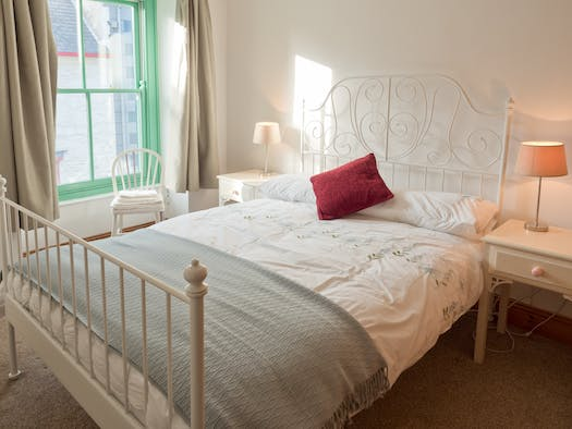 Carpeted double bedroom in Yr Hen Bopty with bed, bedside tables, lamps chair and window
