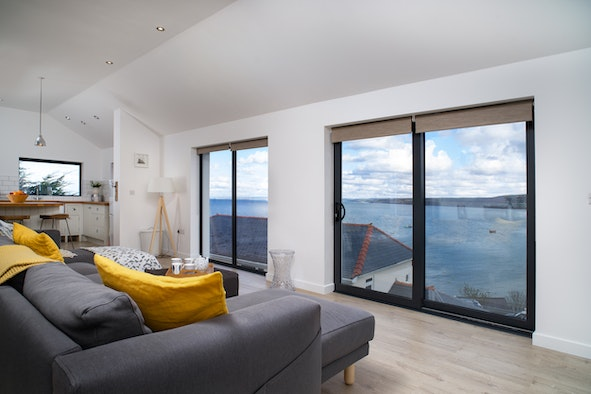 Living area with two sets of double doors with views over the sea at New Quay