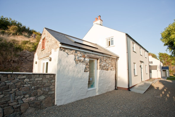 Outside of Boathouse Cottage with front door, gravel driveway