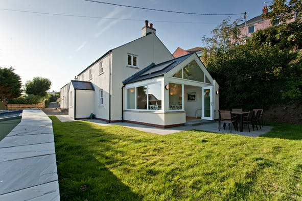 Outside view of Panteg Farmhouse with sun room, patio with table and chairs, lawn